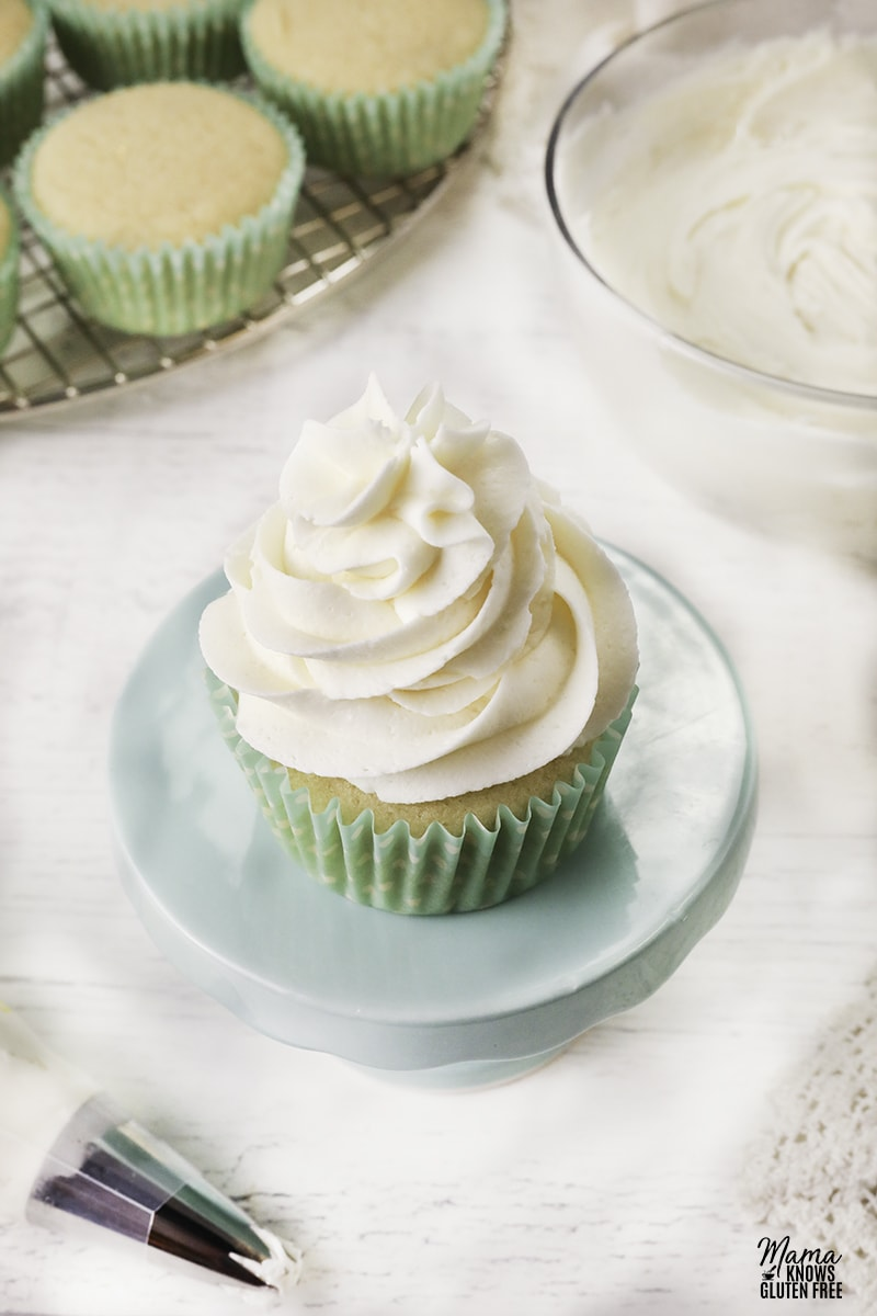 gluten-free vanilla buttercream frosting on a cupcake with vanilla cupcakes and the frosting in the background