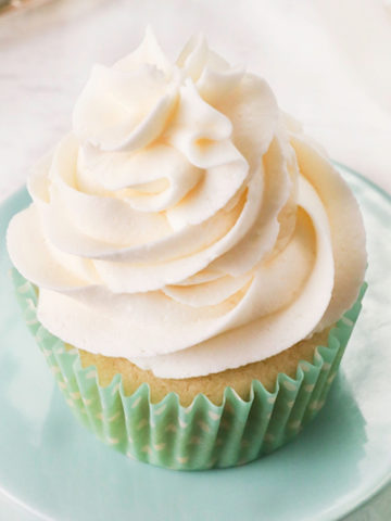 gluten-free frosting piped on top of a vanilla cupcake