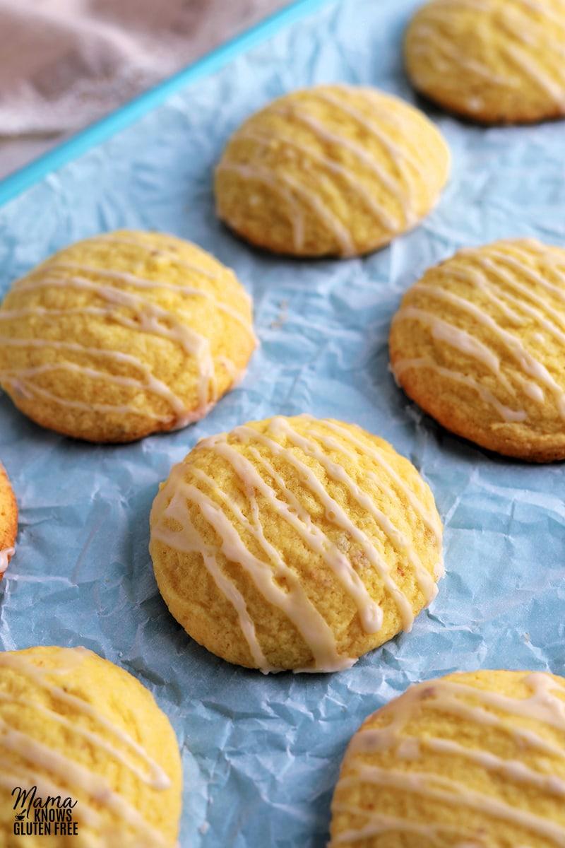 gluten-free lemon cookies with glaze on a blue cookie sheet