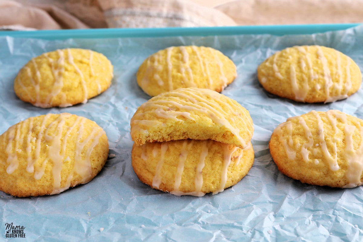 gluten-free lemon cookie with a bite outof it to show the texture ontop of antoher cookie on a blue cookie sheet with other cookies