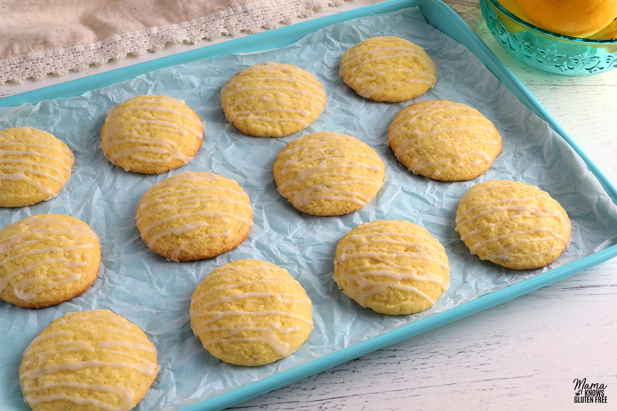 gluten-free lemon cookies on a blue cookie sheet with a bowl of lemons in the background