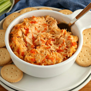 gluten-free appetizer recipe of buffalo chicken dip in a white bowl with crackers