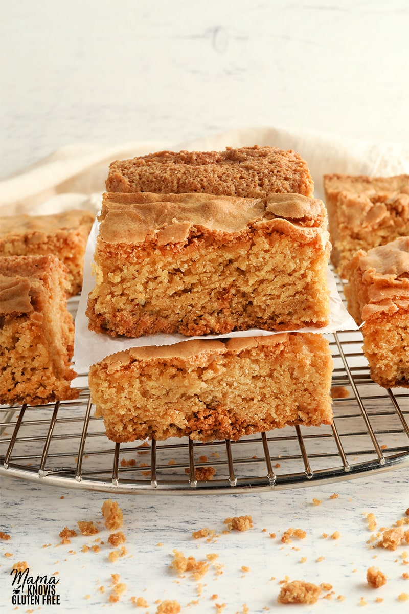 two gluten-free blondies stacked on top of each other with other blondies on a cooling rack