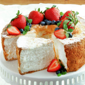 gluten-free and dairy-free angel food cake topped with berries on a white cake stand