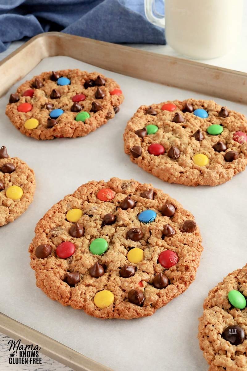 gluten-free monster cookies on a baking sheet with a glass of milk in the background