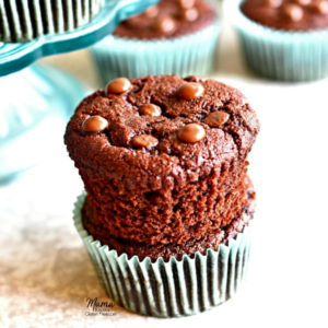 Two Paleo chocolate muffins stacked on top of each other with more muffins in the background