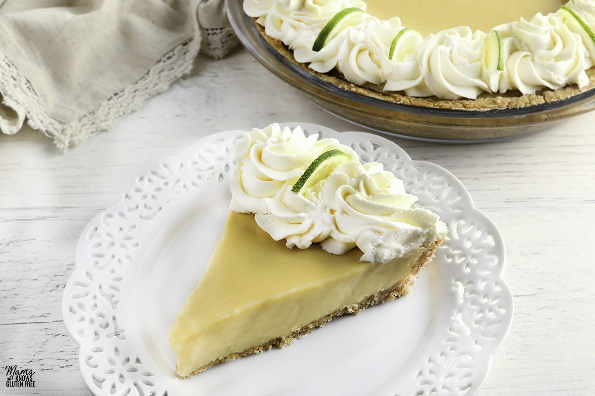 slice of gluten-free key lime pie topped with whipped cream on a plate with the pie in the background
