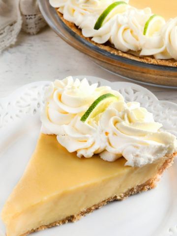 gluten-free key lime pie slice topped with whipped cream on a white plate with the pie in the background