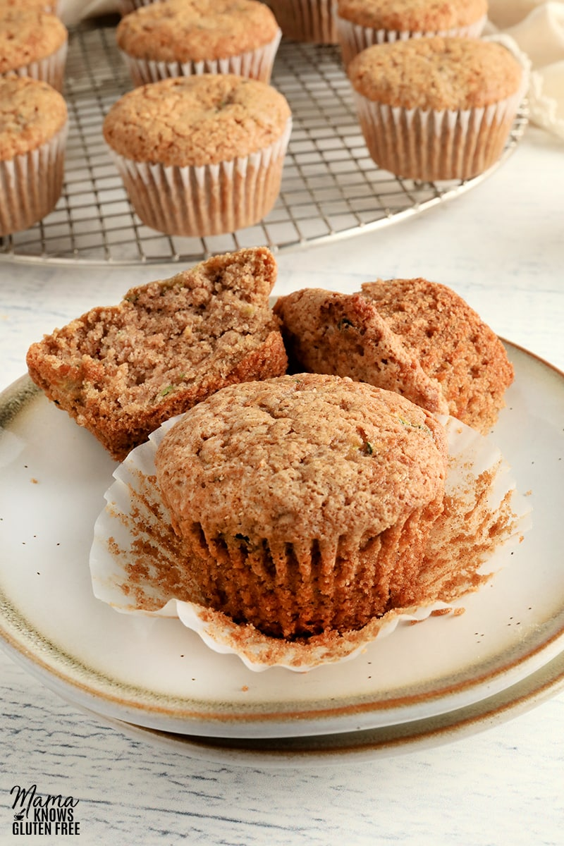 two gluten-free zucchini muffins on white plate with a cooling rack with the muffins in the background