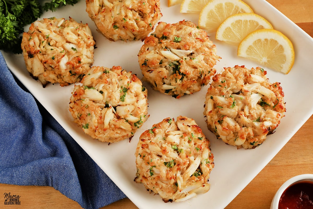 gluten-free crab cakes on a white platter with lemon slices and parsley