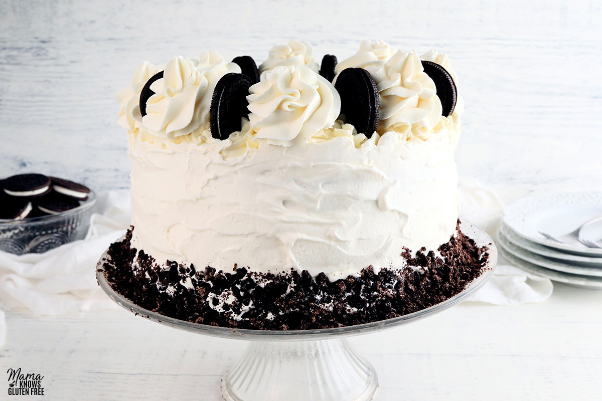gluten-free ice cream cake on a cake plate with plates and bowl of cookies in the background