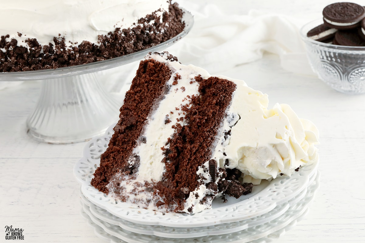 gluten-free ice cream cake slice on a white plate with the cake and chocolate cookies in the background
