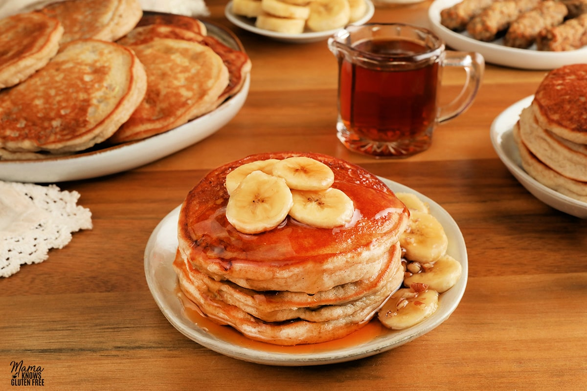 gluten-free banana pancakes on a white plate with syrup, bananas, sausage, and pancakes in the background
