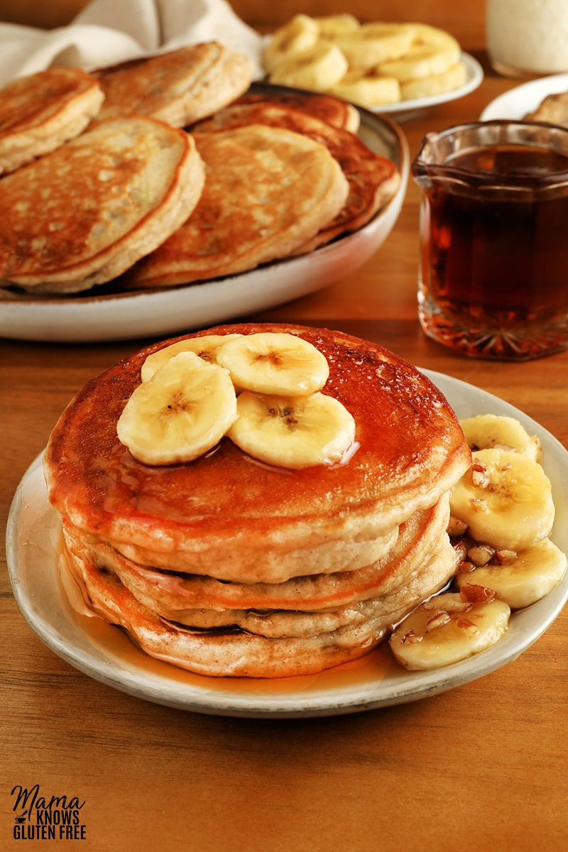 gluten-free banana pancakes in a white plate with sliced bananas, syrup, pancakes and bananas in the background