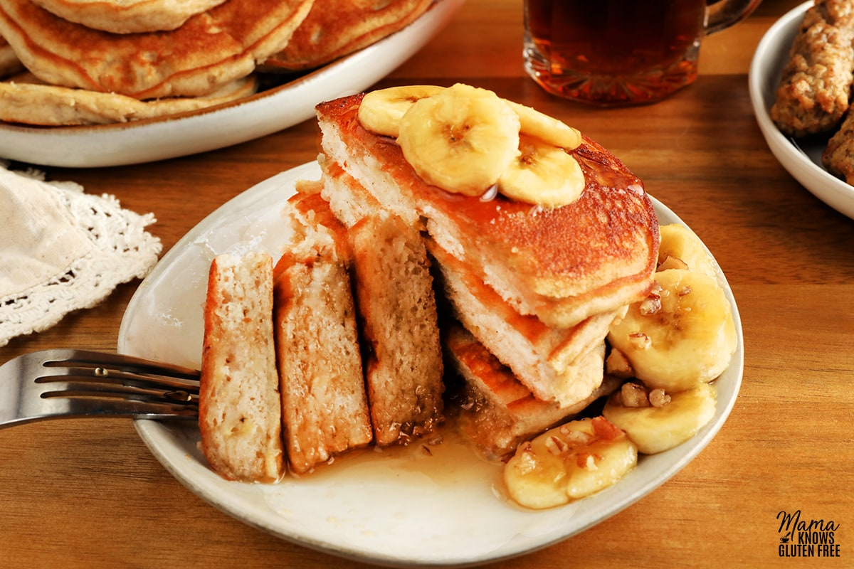 gluten-free banana pancakes stack cut open to show fluffy texture on a white plate, sausage, syrup and pancakes in the background