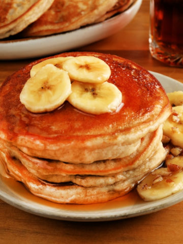 gluten-free banana pancakes on a white plate with syrup and pancakes in the background