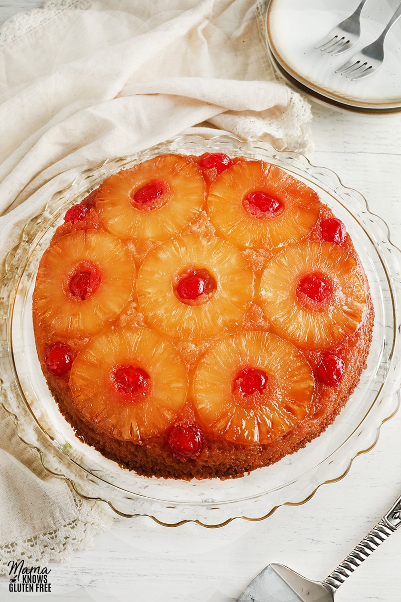 gluten-free pineapple upside down cake on a cake plate with plates and cake cutter in the background