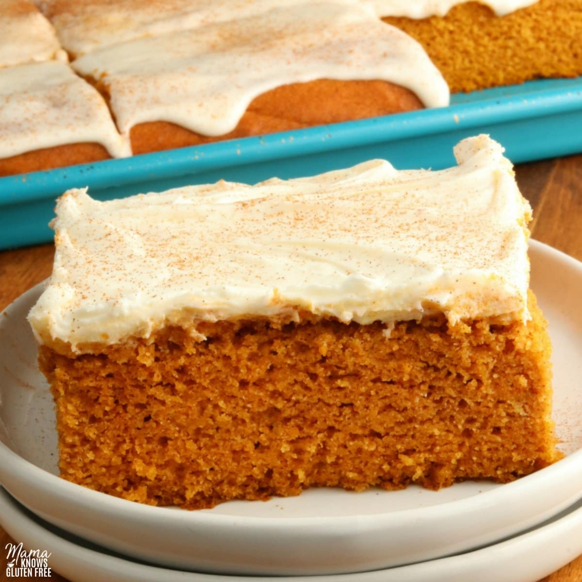 gluten-free pumpkin bar slice on a white plate with the bars in the background