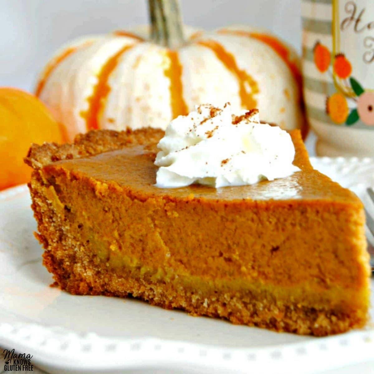 gluten-free pumpkin pie slice on a white plate with pumpkins in the background